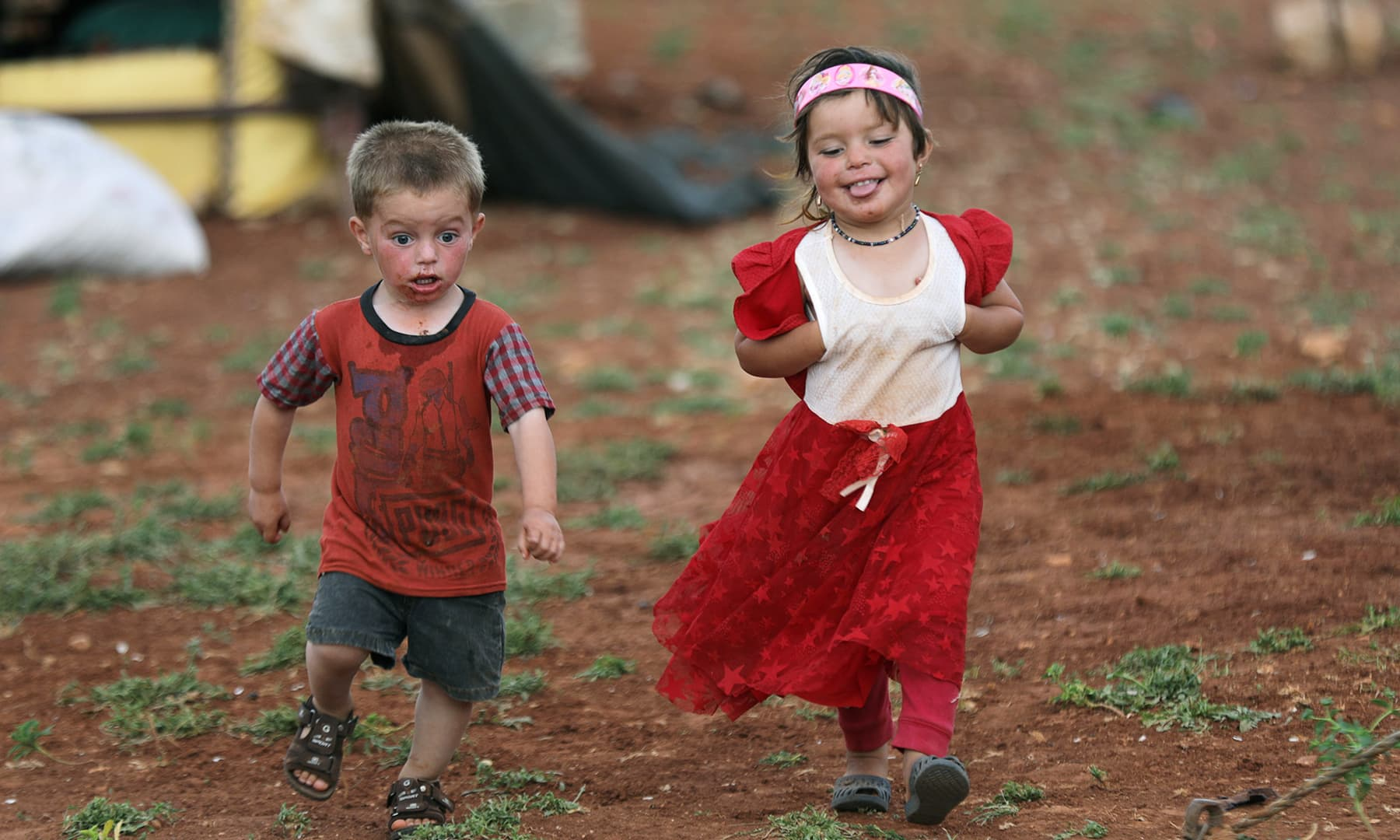 A displaced Syrian refugee girl runs next to a boy during the first day of Eidul Fitr, in an olive grove at the north of Idlib Countryside, Syria on June 4. — Reuters