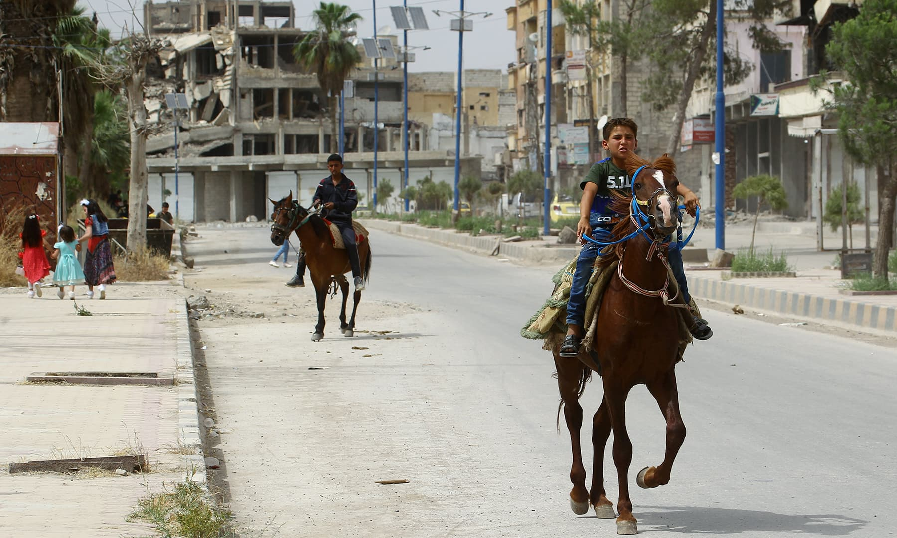 A boy rides on a horse near a damaged building during the first day of Eidul Fitr in Raqqa, Syria on June 5. — Reuters