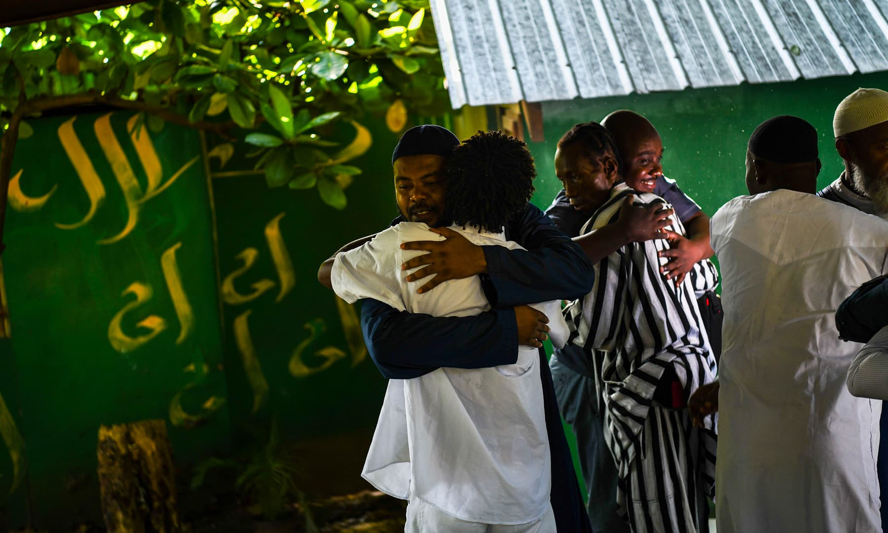 Muslim men hug each other on the occasion of Eidul Fitr at a local mosque in Port-au-Prince, on June 5. — AFP