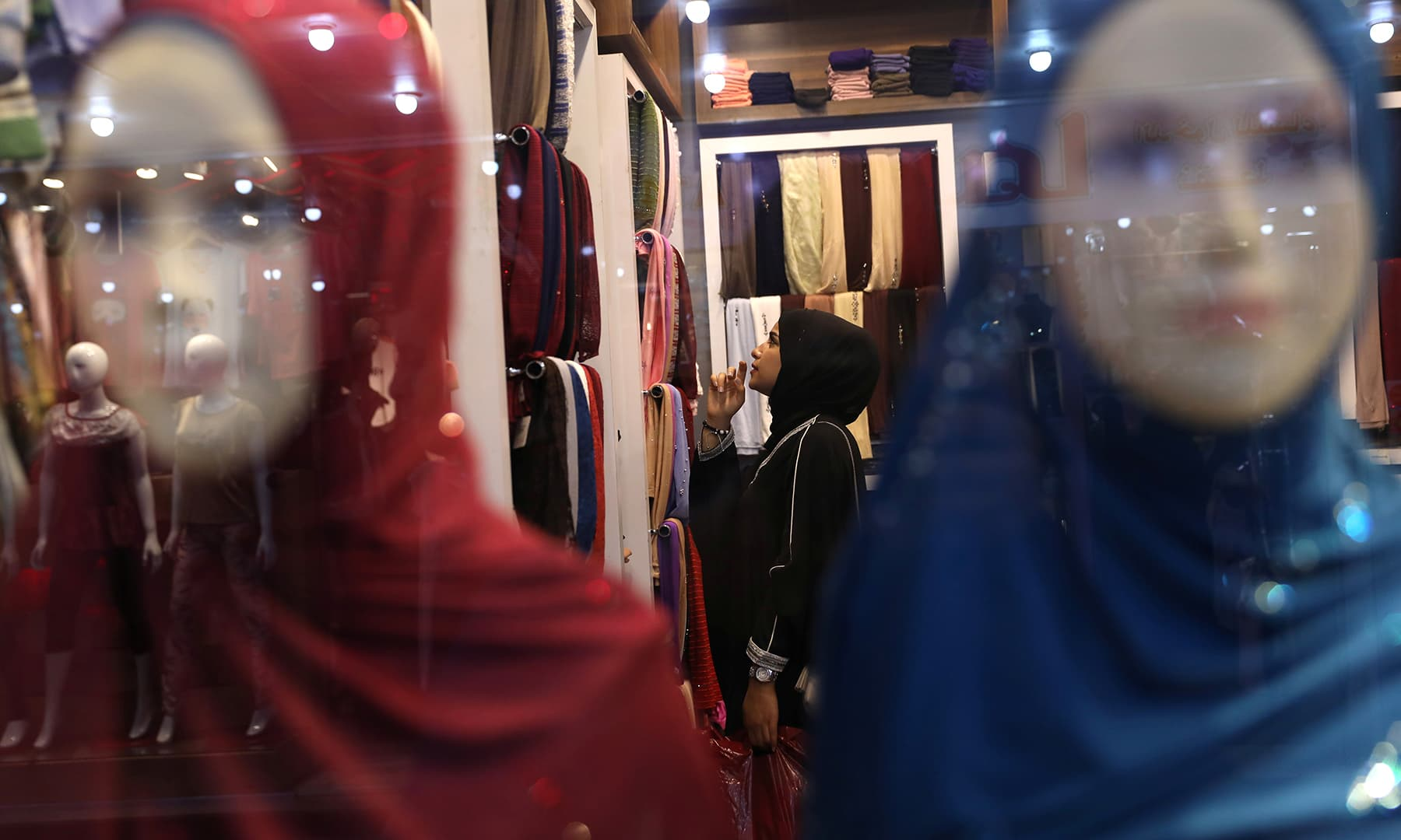 A woman buys clothes in a shop in preparation for Eidul Fitr in Karbala, Iraq on June 4. — Reuters