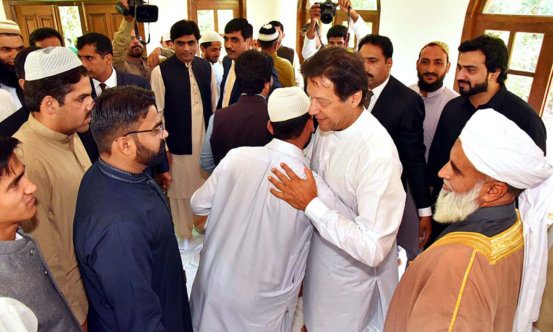Prime Minister Imran Khan greets his staff after Eid prayers on June 5. — APP