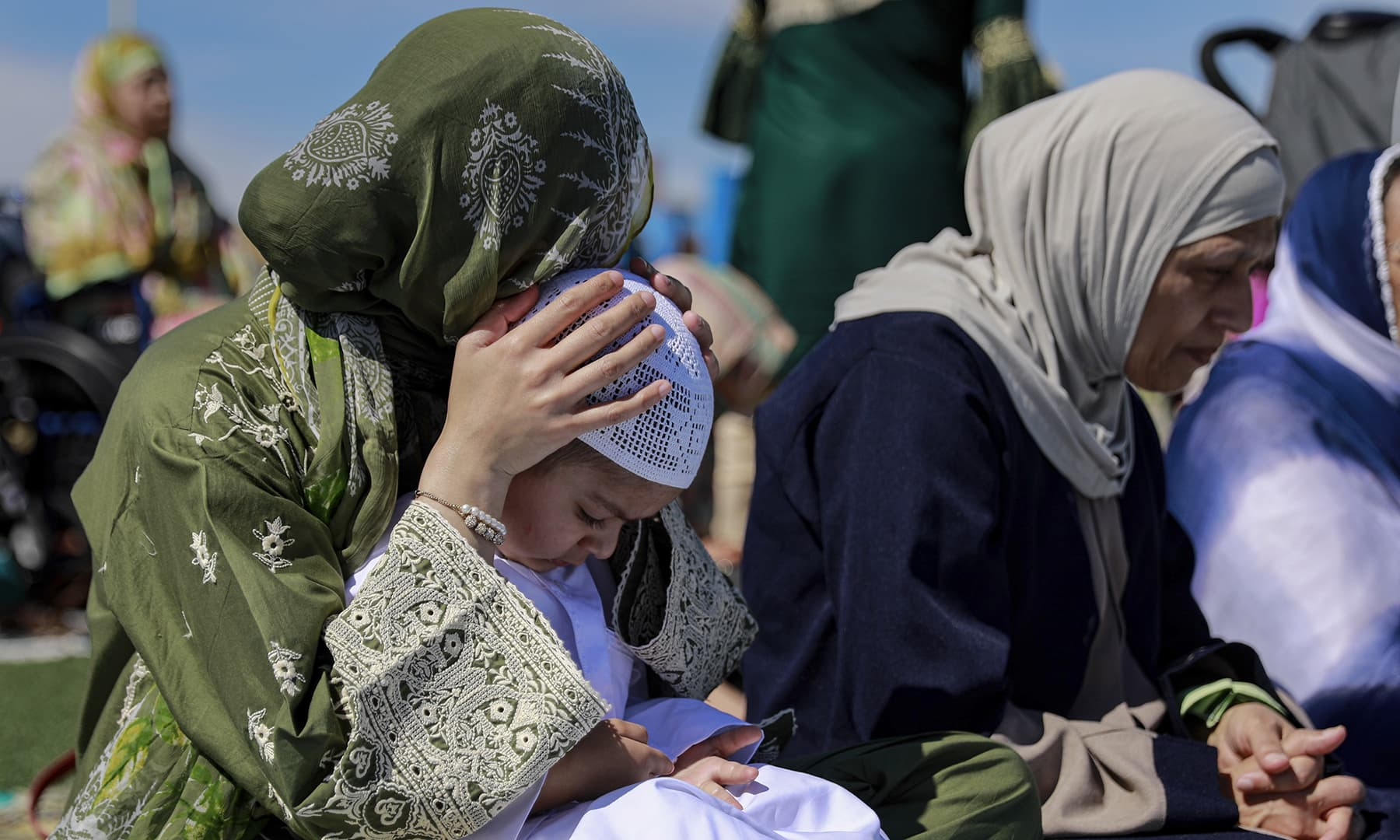 A woman rests her head on her son while holding him after performing Eidul Fitr prayers on the Niles West High School football field in Skokie, Ill, United States on Wednesday, June 5. — AP