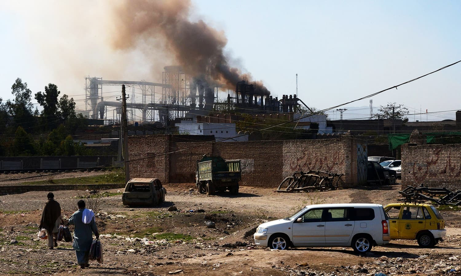 This photograph shows people walking near a factory. — AFP/File