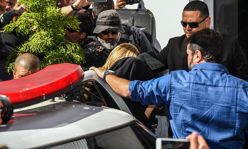 Najila Trindade Mendes de Souza (C-covered with a black jacket) arrives at the Women's Defence Precinct in Sao Paulo, Brazil on Friday. — AFP