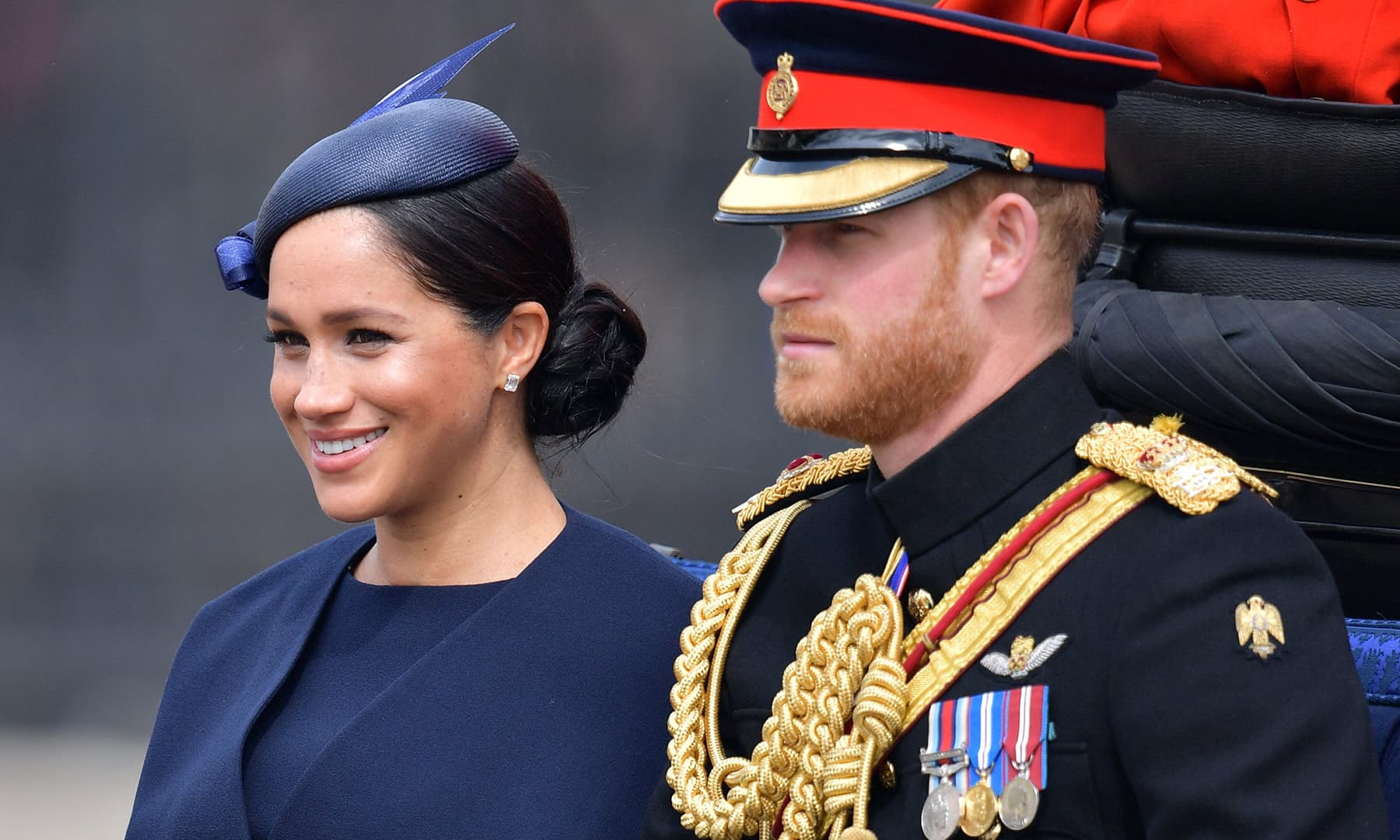 Britain's Meghan, Duchess of Sussex (L) and Britain's Prince Harry, Duke of Sussex (R) make their way in a horse drawn carriage to Horseguards parade ahead of the Queen's Birthday Parade. — AFP