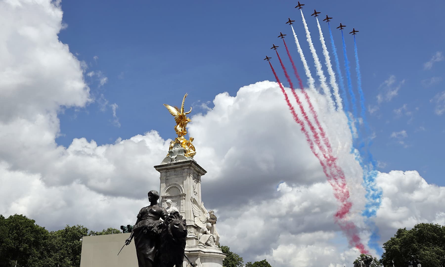 Britain's Red Arrows, the flying display team of the Royal Air Force (RAF) fly over The Queen Victoria Memorial outside Buckingham Palace, watched by members of the Royal Family on the balcony. — AFP