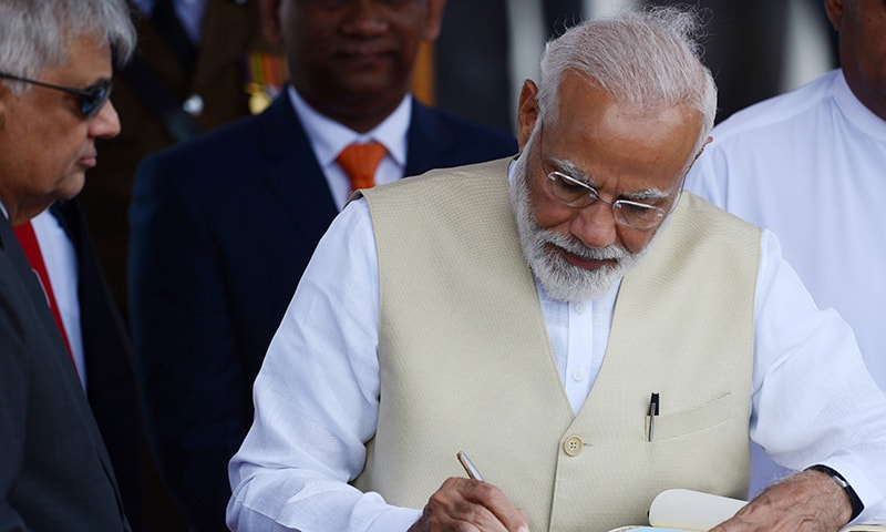 Indian Prime Minister Narendra Modi signs the golden book as Prime Minister of Sri Lanka Ranil Wickremesinghe (L) looks on after his arrival at Bandaranaike International Airport in Katunayake on June 9. — AFP