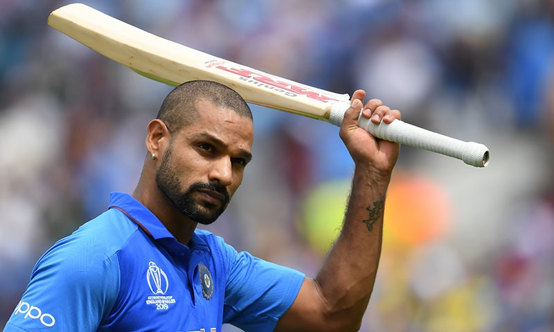 India's Shikhar Dhawan raises his bat to the crowd as he walks back to the pavilion after his dismissal during the 2019 Cricket World Cup group stage match between India and Australia. — AFP