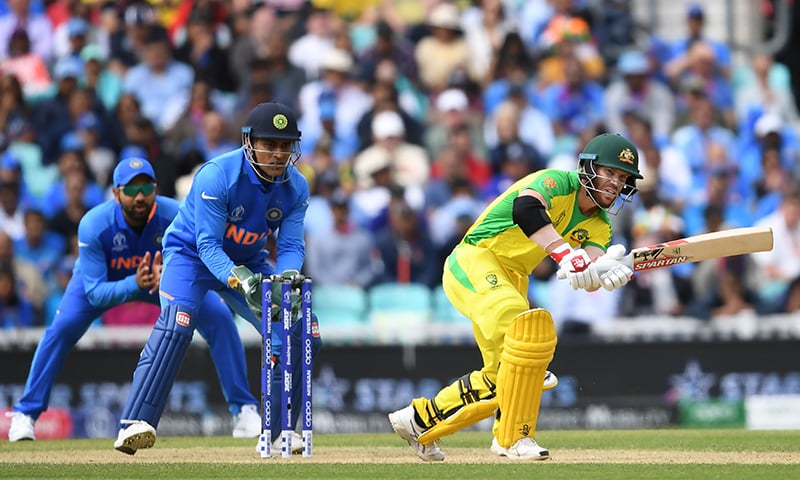 Australia's David Warner (R) is watched by India's Mahendra Singh Dhoni as he plays a shot during the 2019 Cricket World Cup group stage match between India and Australia. — AFP