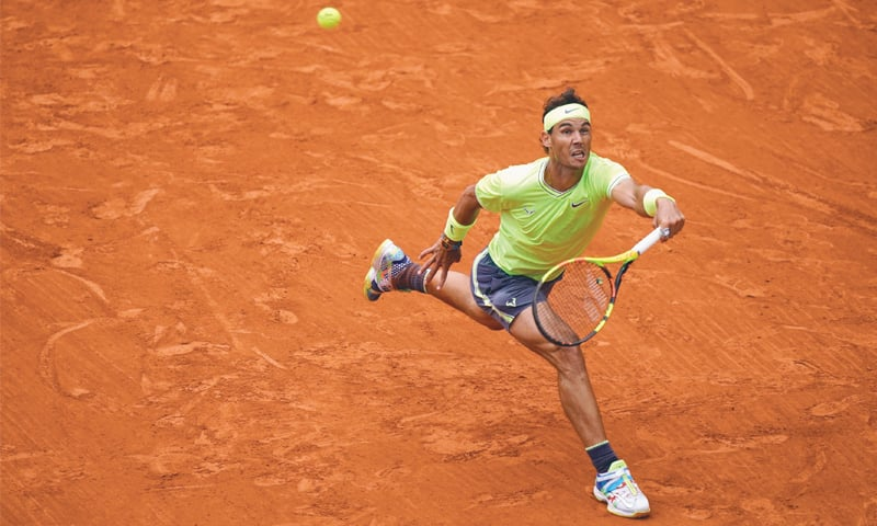 PARIS: Spain's Rafael Nadal hits a return to Dominic Thiem of Austria during the French Open final on Sunday.—AFP