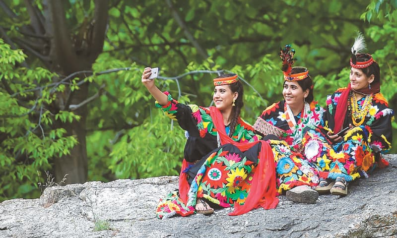 A KALASH woman wearing a traditional dress takes a selfie with her friends during a break as they celebrate 'Joshi', a festival to welcome the arrival of spring, at Bumburate village.—AFP