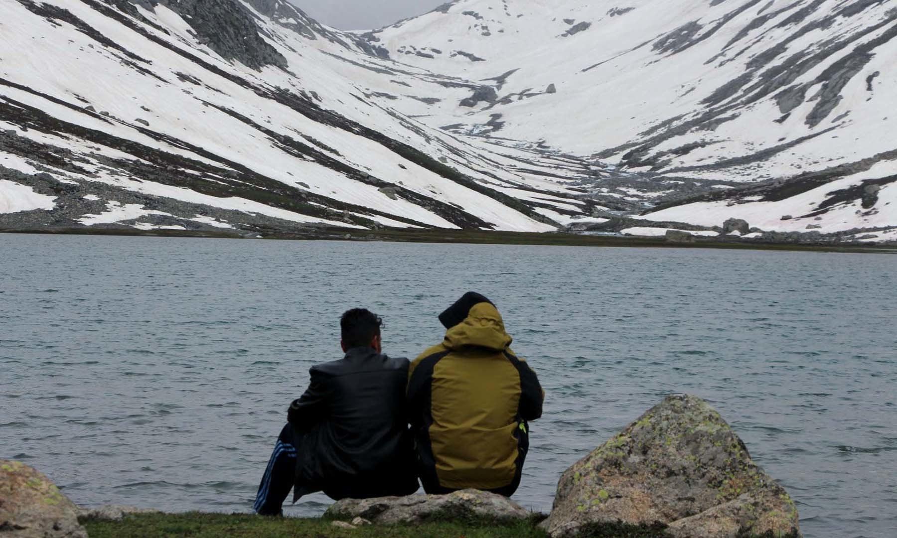 جھیل پر آئی ہوئی ایک ٹیم کے 2 ممبر جھیل کے قریب بیٹھے محوِ گفتگو ہیں—امجد علی سحابؔ