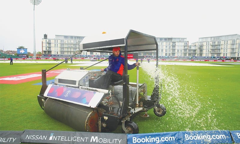 BRISTOL: Ground staff clear water from the pitch at the County Ground on Tuesday.—AP