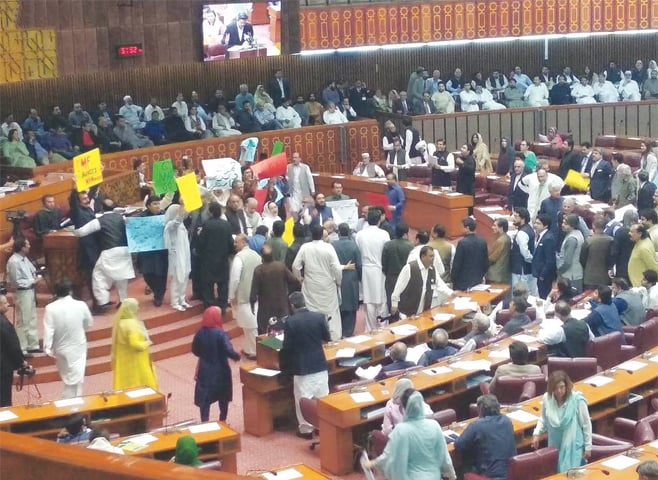 HOLDING aloft banners and shouting slogans, opposition MNAs mount a protest during the budget session on Tuesday.—INP