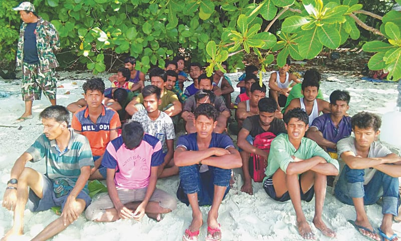 Rohingya men are seen on a beach after a fishing boat carrying them was found at Thailand's Rawi island, near Malaysia. — Reuters
