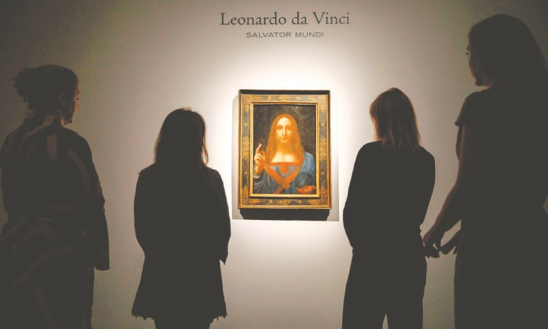 LONDON: Employees pose in front of Salvator Mundi, a painting by Leonardo da Vinci, at Christie's auction house in this Oct 22, 2017, file photo. — AFP
