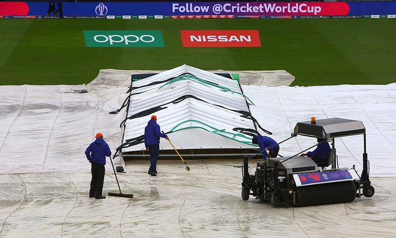 Groundkeepers brush water from the covers as rain delays the start of play ahead of the 2019 Cricket World Cup group stage match between Bangladesh and Sri Lanka at Bristol County Ground in Bristol, southwest England, on June 11. — AFP