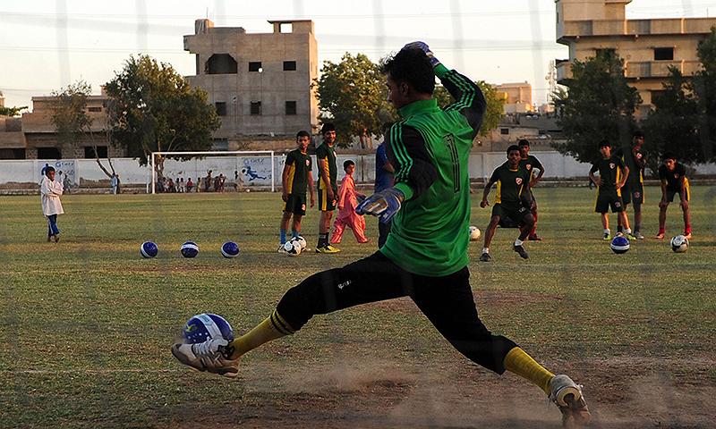 کراچی کے گراؤنڈ میں نوجوان فٹ بال کھیلتے ہوئے — فائل فوٹو/اے ایف پی