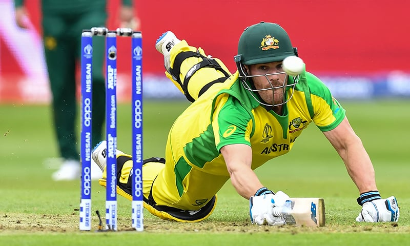 Australia's captain Aaron Finch dives to make his ground as the ball passes the stumps during the 2019 Cricket World Cup group stage match between Australia and Pakistan at The County Ground in Taunton. ─ AFP