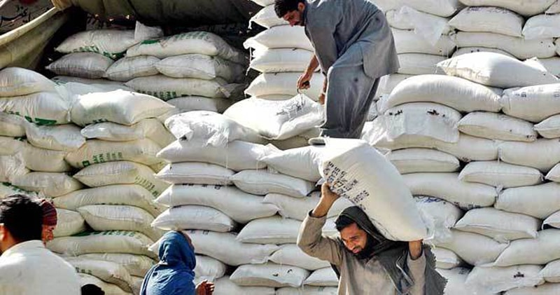 In this file photo labourers are unloading flour bags. The Sindh governement orders inspection of godowns to check hoarding of wheat and flour in the province. No trader is allowed to have a stock of 10,000 bags in their warehouse.