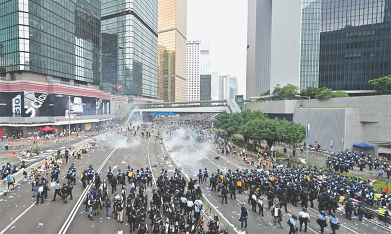 HONG KONG: Protesters run for cover after police fired tear gas during the rally on Wednesday. — AFP