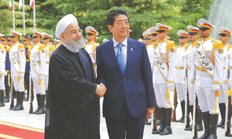 TEHRAN: Iranian President Hassan Rouhani welcomes Japanese Prime Minister Shinzo Abe at the Saadabad Palace on Wednesday. — AFP