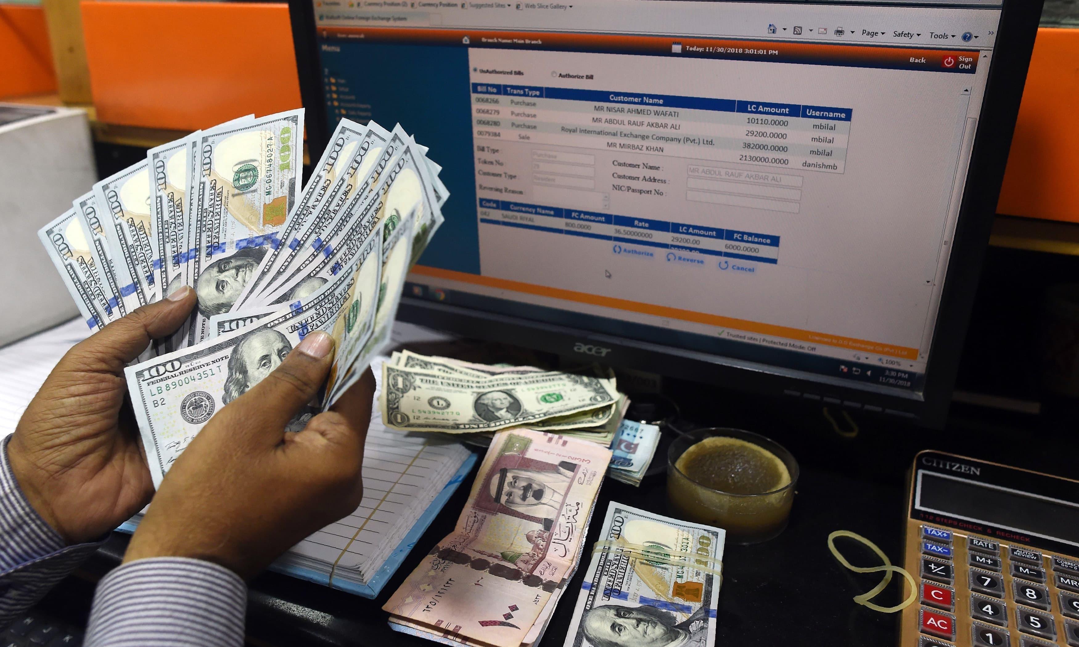 A Pakistani dealer counts US dollars at a currency exchange shop in Karachi on November 30, 2018. — AFP/File