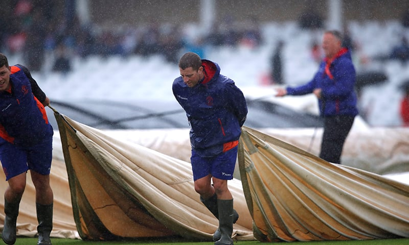 Groundstaff at Trent Bridge put covers on the pitch as rain delays World Cup match between India and New Zealand. — Reuters