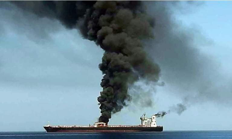 A picture from Iranian State TV IRIB on June 13 reportedly shows smoke billowing from a tanker said to have been attacked off the coast of Oman. — AFP