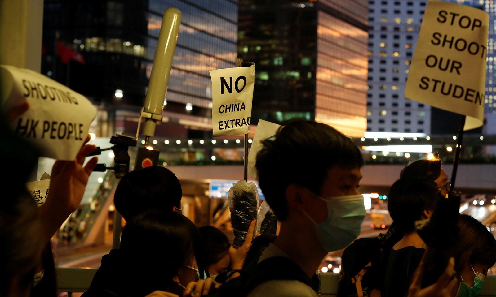 اس دوران مظاہرین مقامی اور دیگر زبانوں میں پلے کارڈز اٹھائے ہوئے نظر ٓئے — فوٹو: رائٹرز