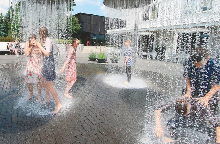 VILNIUS: Children play under showers at a public fountain to cool off.—AFP