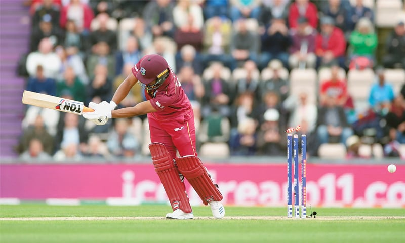SOUTHAMPTON: West Indies opener Evin Lewis is cleaned up by England pacer Chris Woakes during their match at the Rose Bowl on Friday.—Reuters