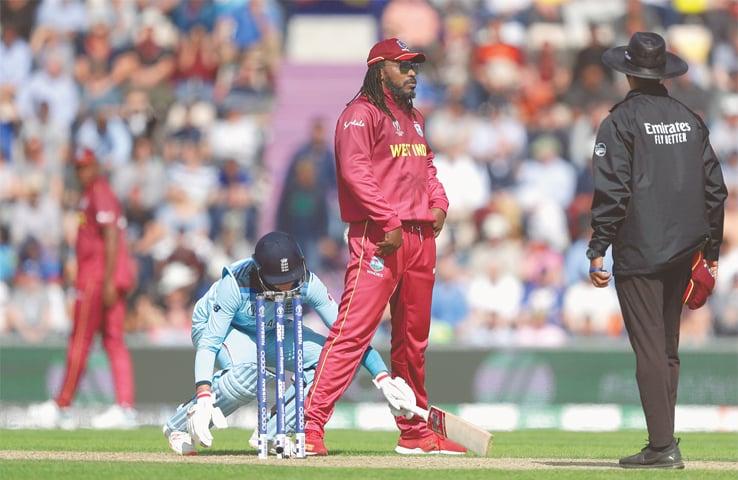 WEST INDIES' Chris Gayle jokingly blocks the way of England batsman Joe Root as he tries to complete a run.—AP