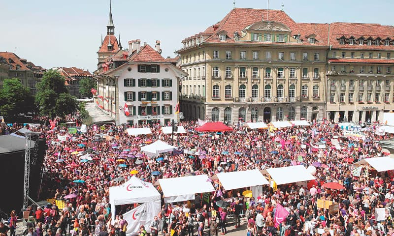 BERN: Women gather for a rally in front of the federal palace on Friday.—AFP