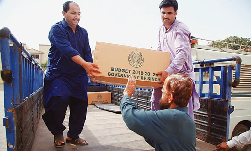 Workers unload budget documents outside the Sindh Assembly building on Friday. — PPI