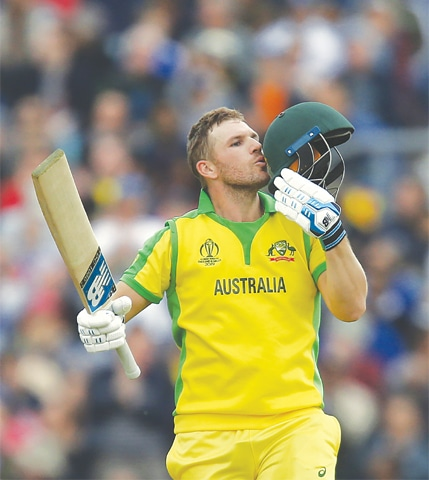 Australia captain Aaron Finch kisses the helmet after reaching his century.—AFP