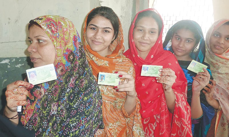 Women display their national identity cards while waiting in line to cast their votes