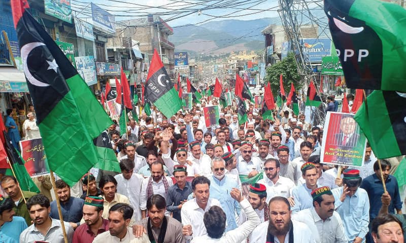 PPP workers pass through a bazaar during a rally in Lower Dir. — INP