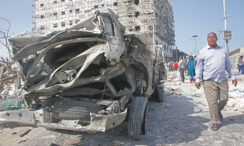 Mogadishu: A man walks past the wreckage of an official vehicle that was destroyed in a bomb attack on Saturday. —AP