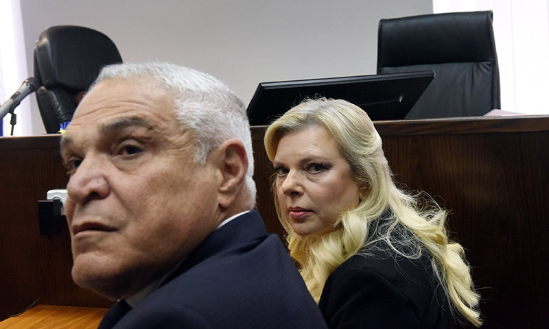 Israeli Prime Minister Benjamin Netanyahu's wife, Sara, and her lawyer, Yossi Cohen, wait for the judge to arrive before the start of a hearing on a plea bargain over misuse of state funds for meals, at the Magistrate Court in Jerusalem on June 16. — Reuters