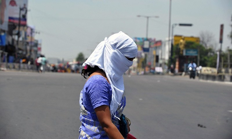 An Indian woman with her face covered crosses a road on the outskirts of Hyderabad. — AFP/File