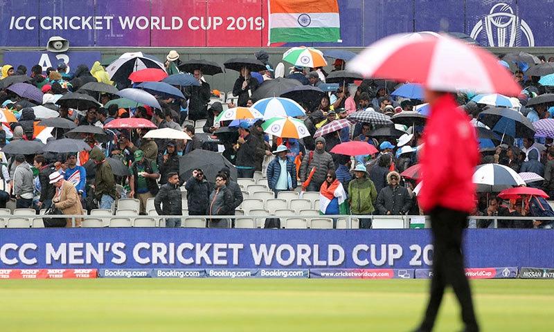 بارش کے سبب شائقین کرکٹ نے اپنی چھتریاں نکالی ہوئی ہیں تاکہ برسات کے پانی سے بچا جا سکے— فوٹو: اے پی