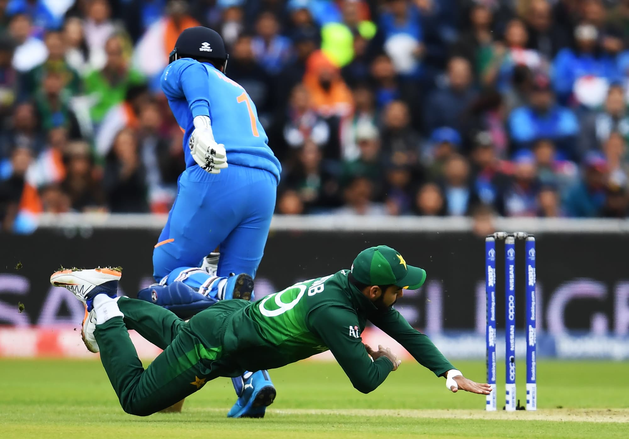 K.L. Rahul (L) makes his ground as Shadab Khan makes a run out attempt. ─ AFP