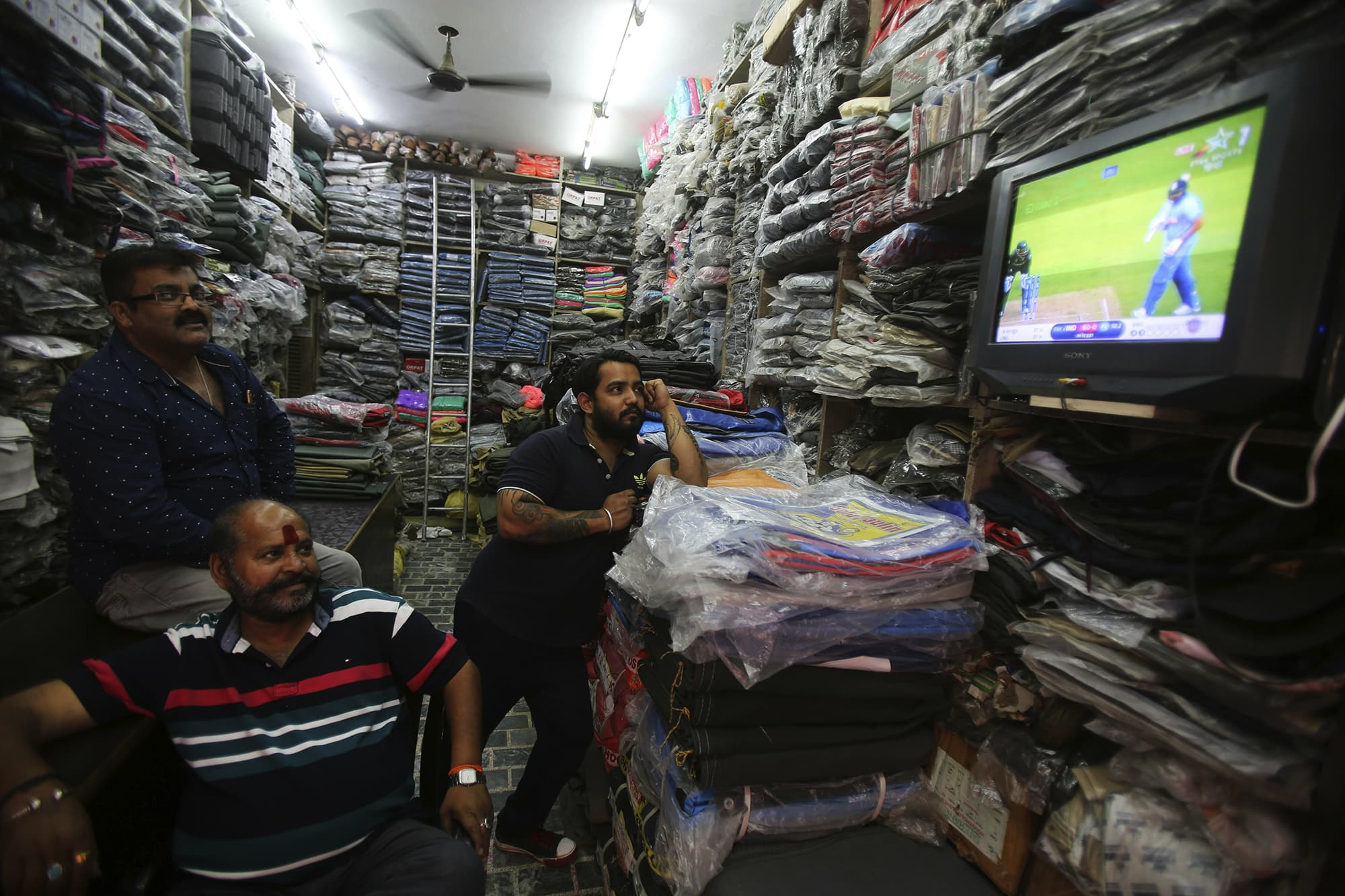 Men working at a textile shop in Jammu, IoK, watch the match on TV. ─ AP