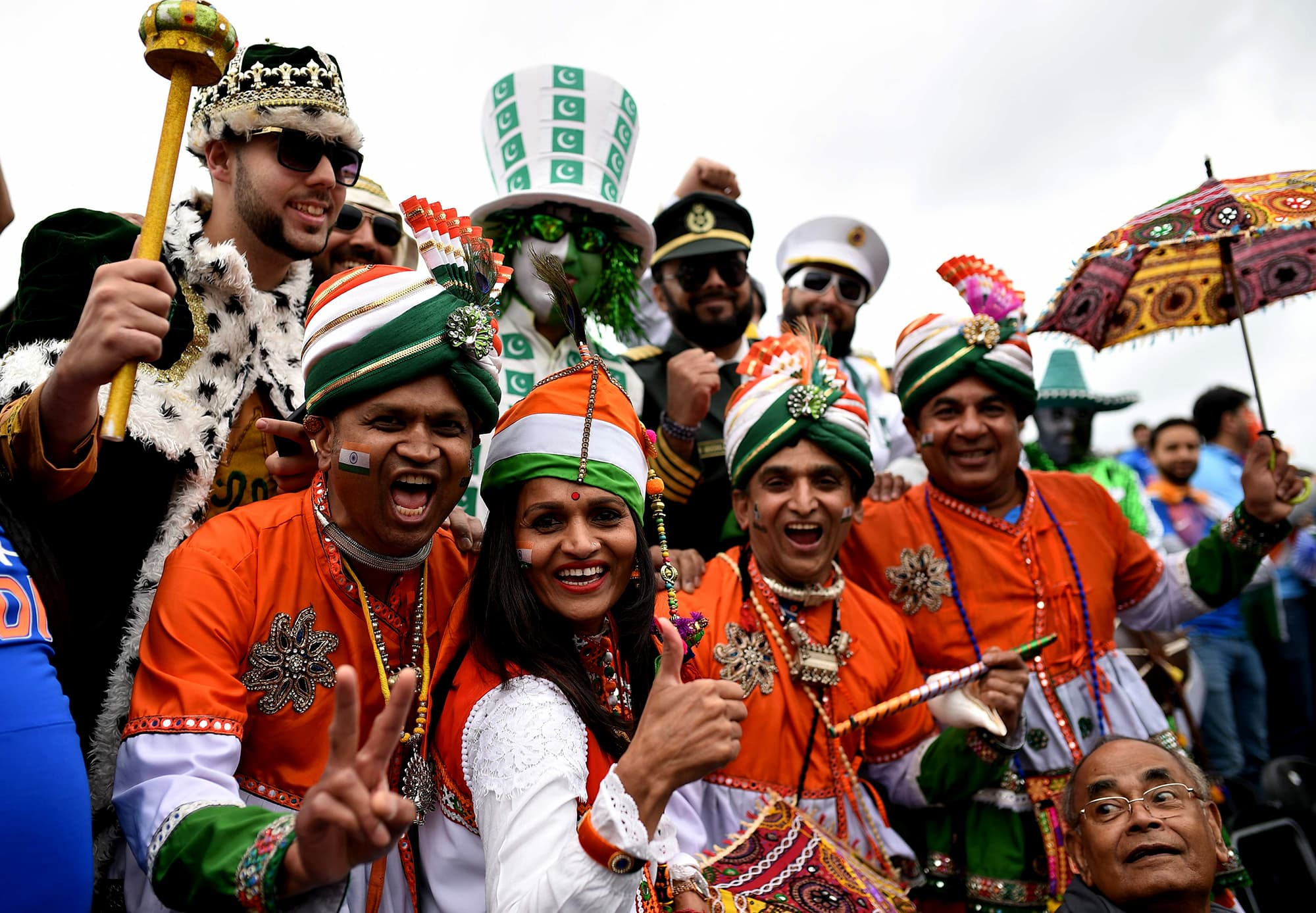 Indian fans in costume jump into the frame with Pakistani fans in costume. ─ AFP