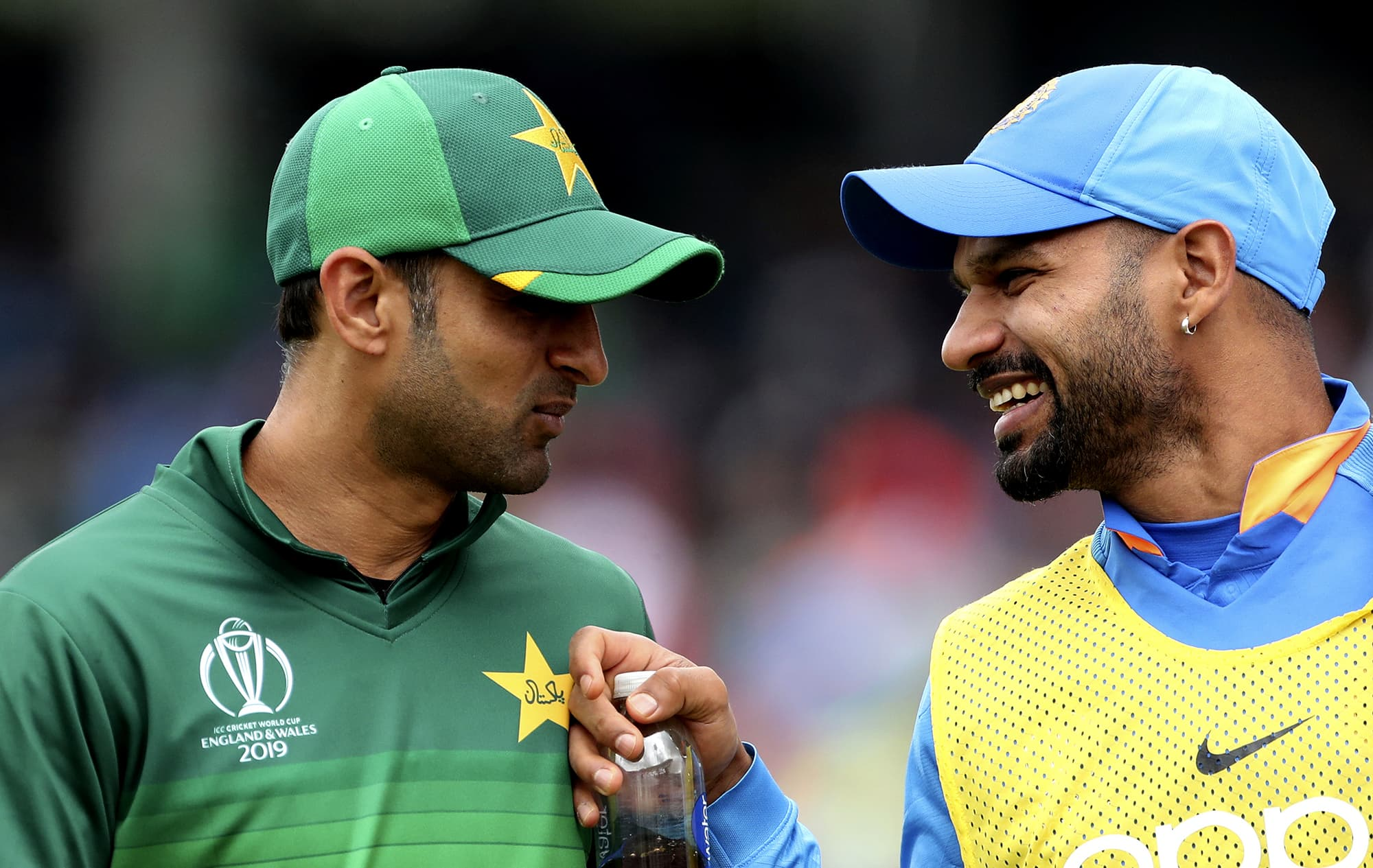 Shoaib Malik shares a light moment with Shikhar Dhawan during the drinks break. ─ AP