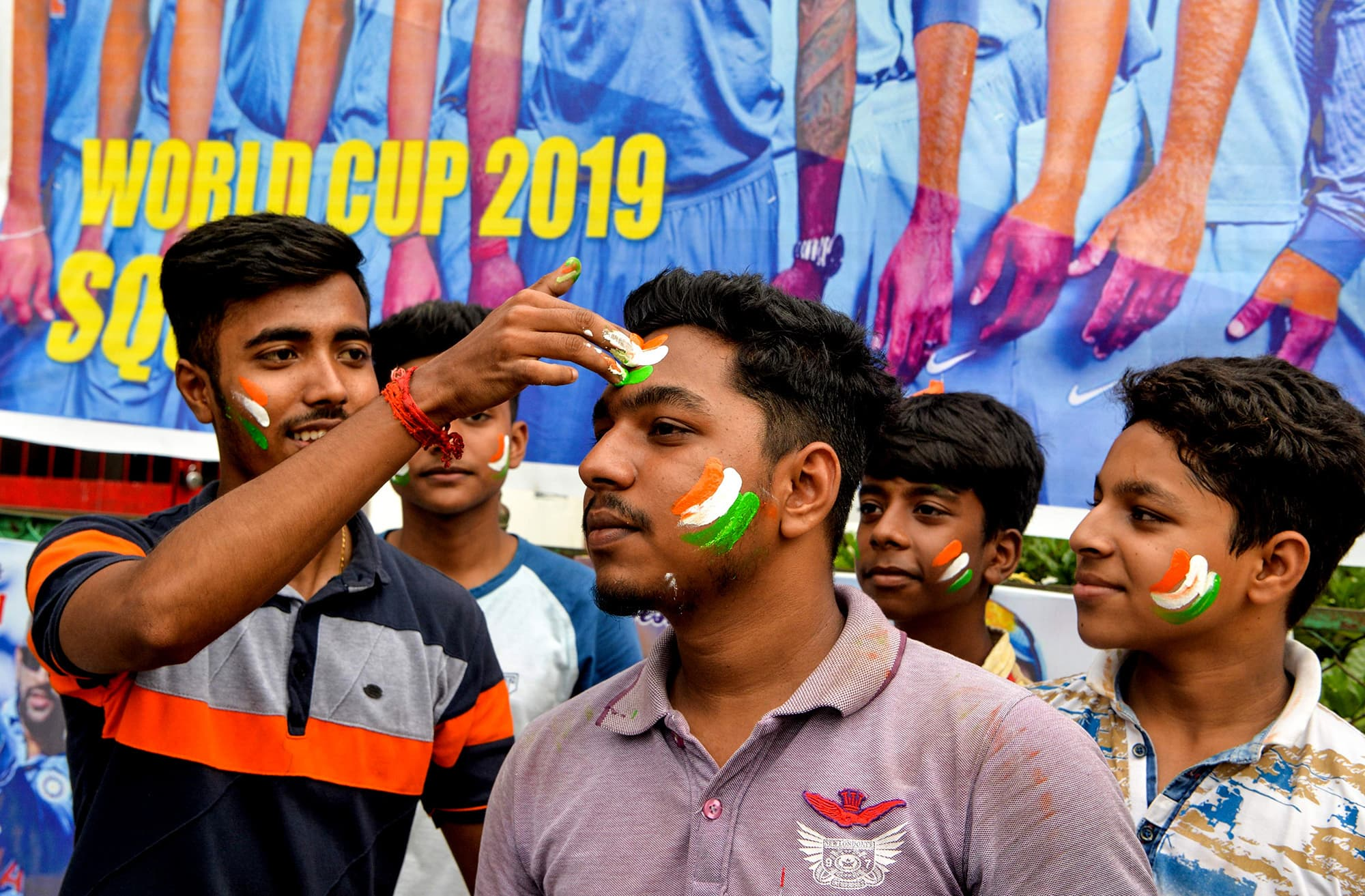 Indian fans paint their faces with colours of their national flag in Siliguri. ─ AFP