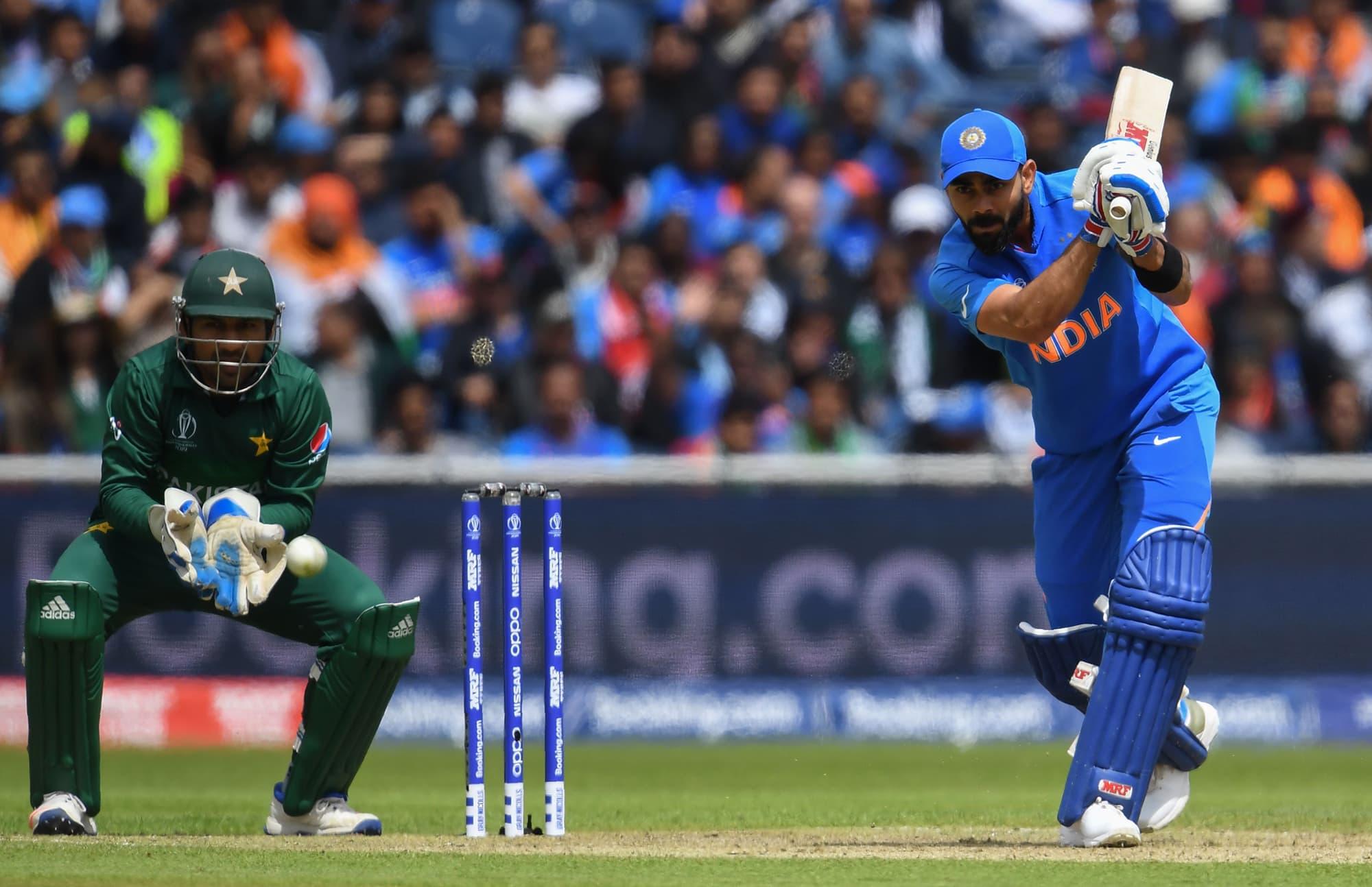 Virat Kohli (R) plays a shot as Sarfaraz looks on. ─ AP