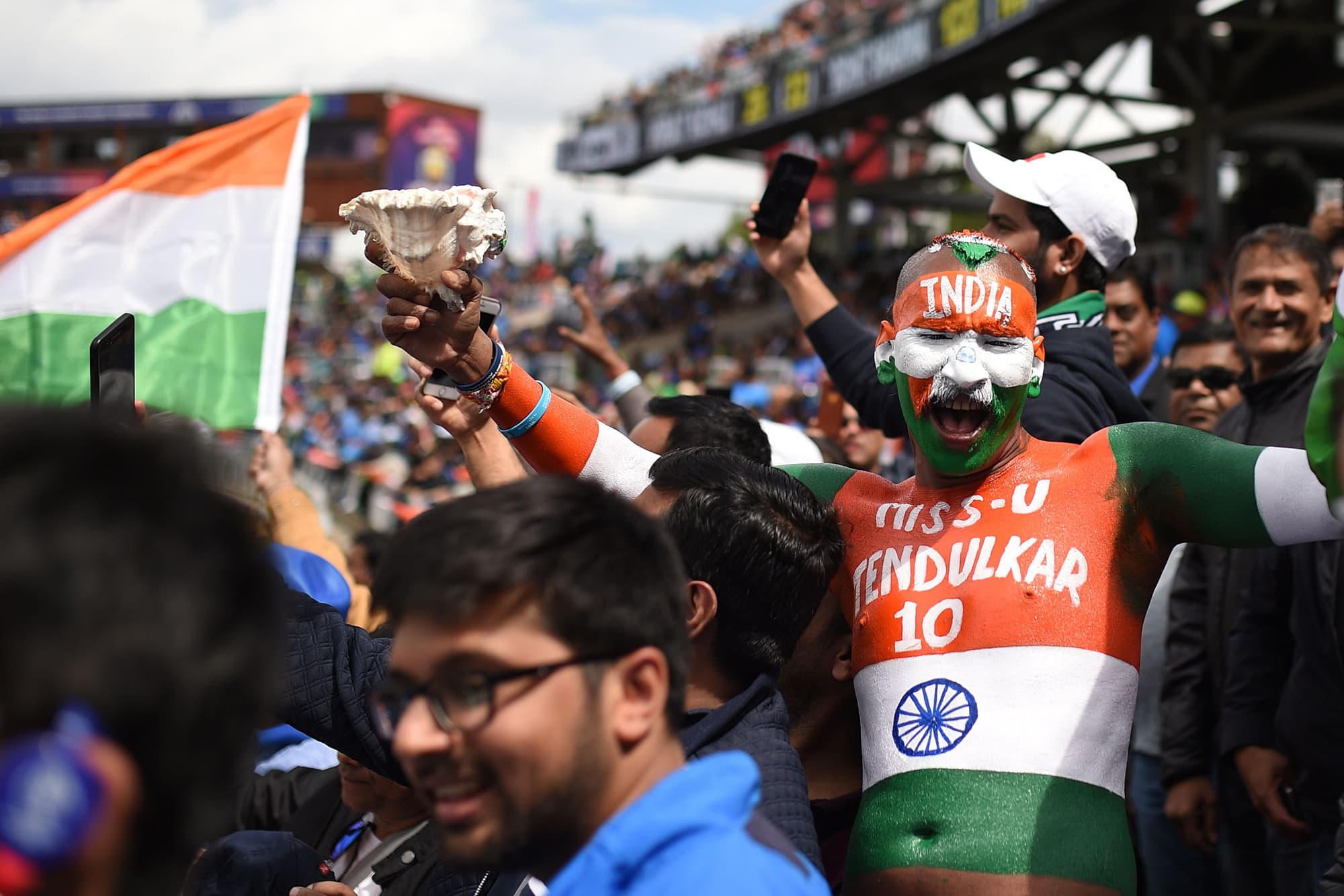An Indian fan painted in the national colours poses for a photograph in the crowd. — AFP