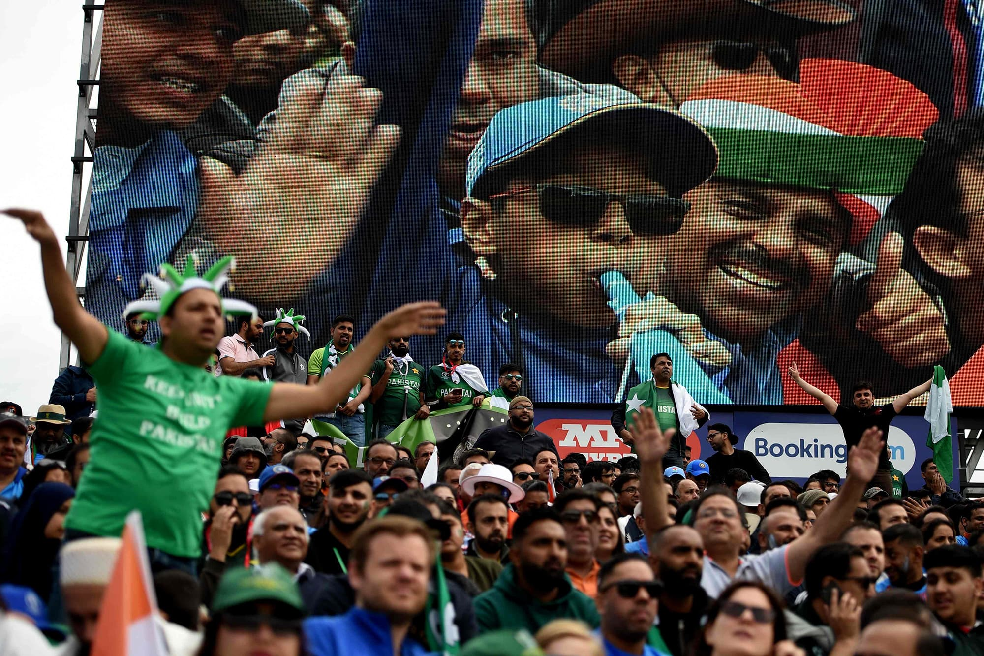 Indian and Pakistani supporters cheer on their teams during the match. ─ AFP
